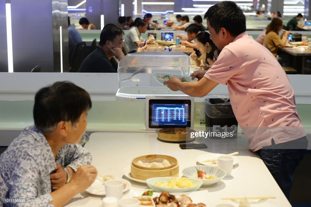 This photo taken on July 30, 2018 shows a man (R) getting food from a robot at the ROBOT.HE restaurant in Shanghai. - The little robotic waiter wheels up to the table, raises its glass lid to reveal a steaming plate of local Shanghai-style crayfish and announces in low, mechanical tones, 'Enjoy your meal.' (Photo by - / AFP) / China OUT / TO