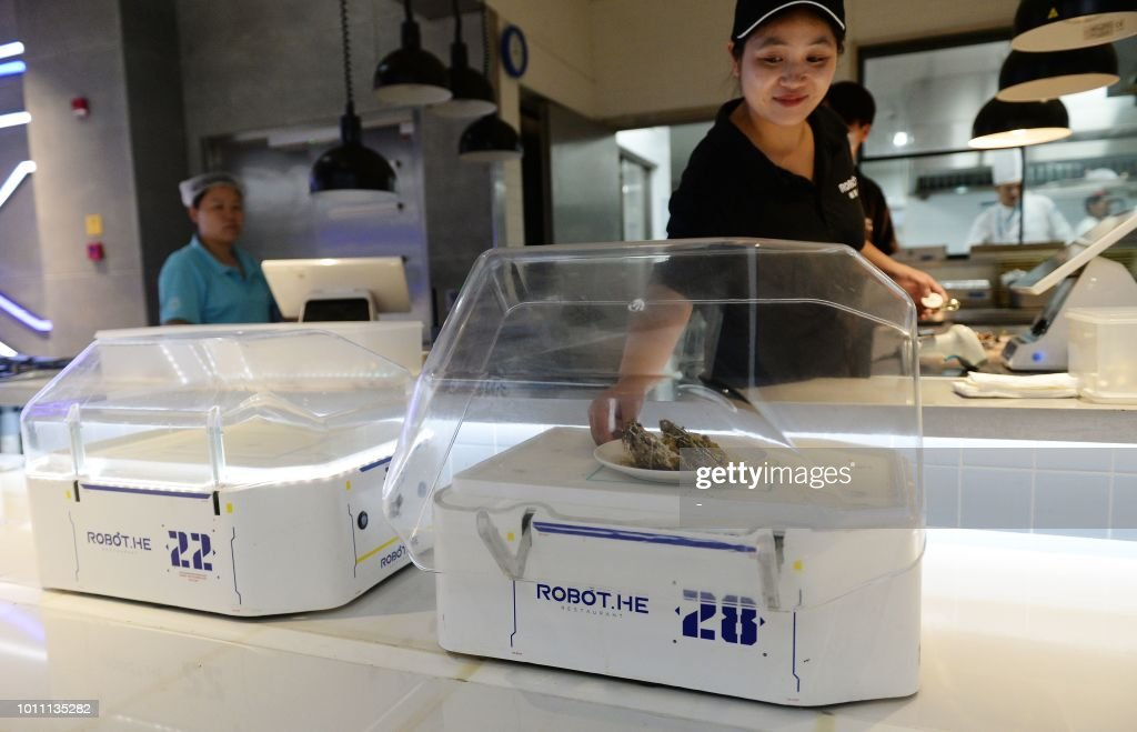 This photo taken on July 30, 2018 shows a staff member placing food on a robot at the ROBOT.HE restaurant in Shanghai. - The little robotic waiter wheels up to the table, raises its glass lid to reveal a steaming plate of local Shanghai-style crayfish and announces in low, mechanical tones, 'Enjoy your meal.' (Photo by - / AFP) / China OUT / TO
