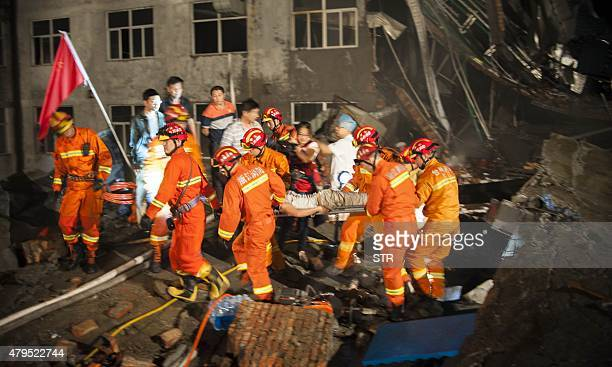 This photo taken on July 4 2015 shows rescuers carrying a victim in the debris of a collapsed building in Wenling east China's Zhejiang province Nine...