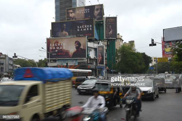 This photo taken on July 4 2018 shows Indian commuters travelling past large billboards for 'Sacred Games' the upcoming Indian series on Netflix in...