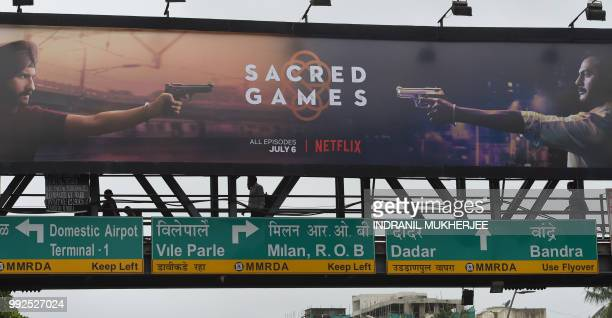 This photo taken on July 4 2018 shows Indian commuters walking below a poster of 'Sacred Games' the upcoming Indian series on Netflix in Mumbai...