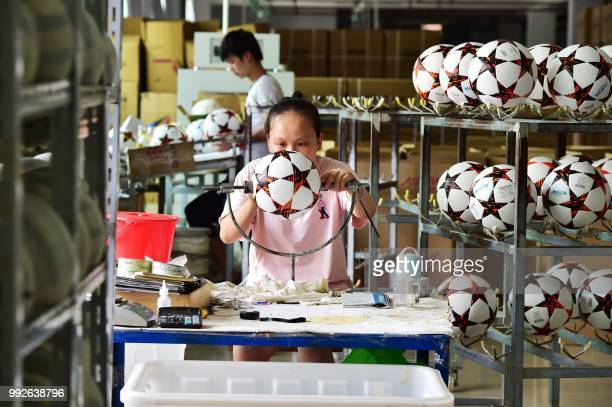 This photo taken on July 5, 2018 shows a worker making footballs that will be exported to Russia and Brazil at a factory in Yiwu in China's eastern...