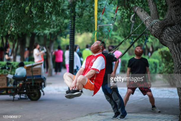 This photo taken on July 5, 2020 shows a man doing exercise as he hangs on a tree in Shenyang in China's northeastern Liaoning province. / China OUT