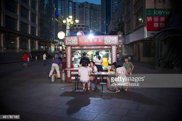 This photo taken on July 6 2014 shows people enjoying their evening meal in a street of the northeastern Chinese port city of Dalian Al fesco dining...