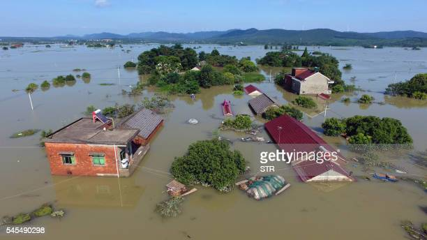 This photo taken on July 7, 2016 shows an overview of trees and houses submerged by floodwater in a village in Xuancheng, in east China's Anhui...