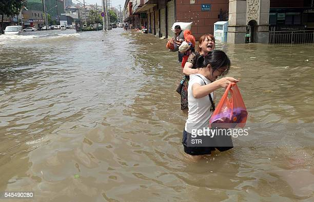 This photo taken on July 7 2016 shows residents making their way through a flooded street in Wuhan in central China's Hubei province Flooding is...