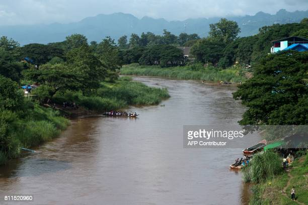 This photo taken on July 7 2017 shows migrant workers crossing the border between Thailand and Myanmar in a boat in Moei River near Mae Sot Tak...