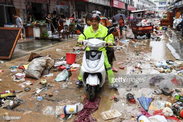 This photo taken on July 7, 2020 shows a man riding a scooter passing a street after heavy rains caused flooding in Shexian county, Huangshan city,...