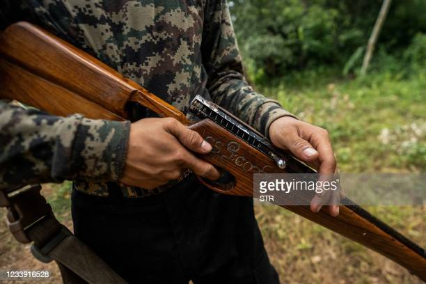 """This photo taken on July 7, 2021 shows a member of the Karenni People Defense Force holding a homemade gun adorned with the words """"Spring Revolution""""..."""