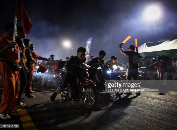 This photo taken on July 9 2017 shows Thai youths racing each other on motorbikes during an 'NGO Street Drag Bike Party' a legal racing event in the...