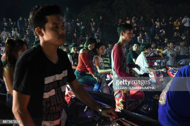 This photo taken on July 9 2017 shows Thai youths waiting to race each other during an 'NGO Street Drag Bike Party' a legal racing event in the...