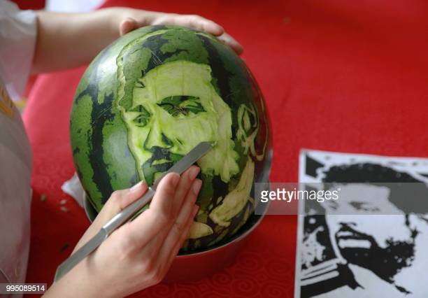 This photo taken on July 9 2018 shows a high school student carving an image of Egypt's forward Mohamed Salah on a watermelon in Shenyang in China's...