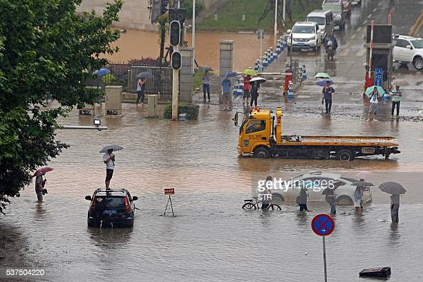 This photo taken on June 1 2016 shows residents making their way through a flooded street in Wuhan central China's Hubei province A heavy rainstorm...