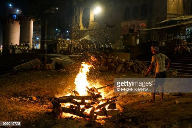 This photo taken on June 1, 2018 shows an Indian member of the Dom community tending to a funeral pyre at the Manikarnika ghat in the old quarters of...