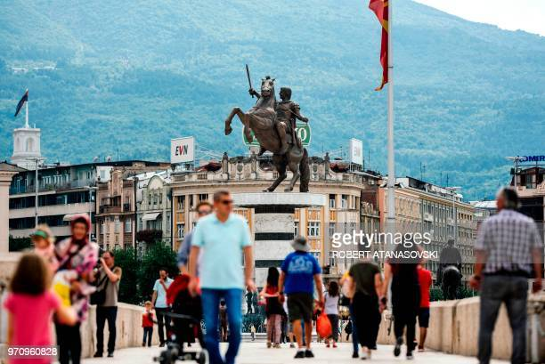 This photo taken on June 10 shows people crossing the old bridge of the Vardar river in front of the monument of King Alexander the Great in the...