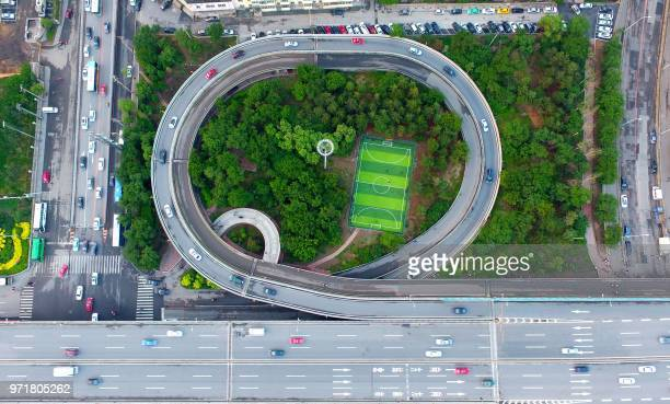TOPSHOT This photo taken on June 11 2018 shows an aerial view of a football pitch located nearby an interchange in Shenyang in China's northeastern...