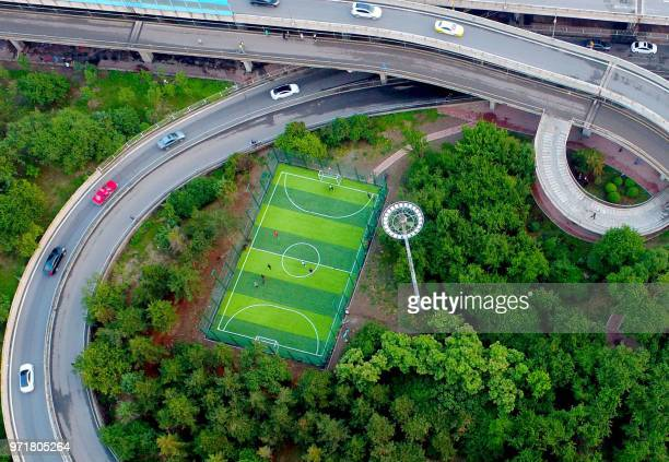 This photo taken on June 11 2018 shows an aerial view of a football pitch located nearby an interchange in Shenyang in China's northeastern Liaoning...