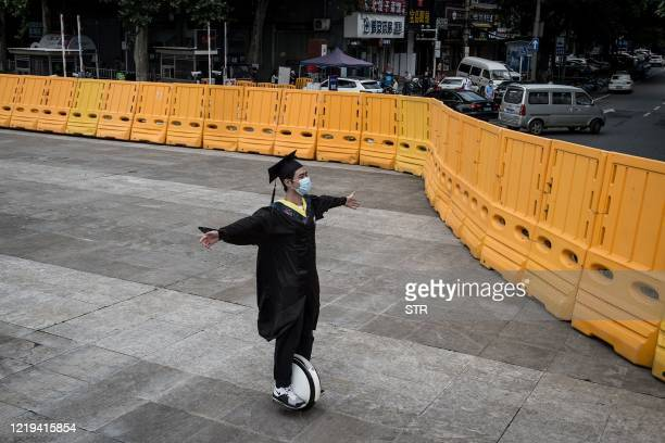 TOPSHOT This photo taken on June 11 2020 shows a university graduate clad in academic dress riding a hoverboard in front of the Huazhong University...