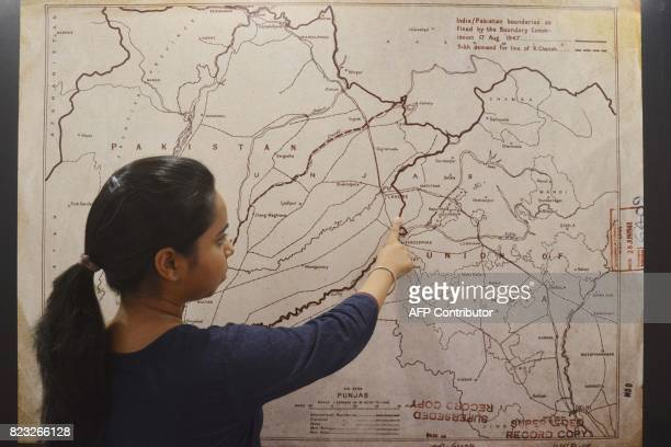 This photo taken on June 14, 2017 shows an Indian woman looking at a map of the India-Pakistan boundaries as fixed by the boundary commission on...