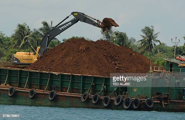 This photo taken on June 16 2016 shows a barge being loaded with nickel ore at a private port in Infanta town Pangasinan province north of Manila...