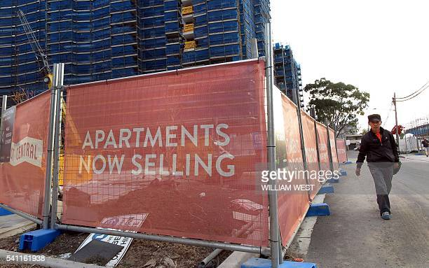 This photo taken on June 17 2016 shows a man walking past an apartment block under construction in Sydney Sydney is imposing new taxes on foreigners...