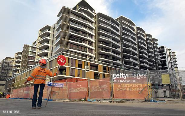 This photo taken on June 17 2016 shows a worker holding a stop sign in front of an apartment block under construction in Sydney Sydney is imposing...