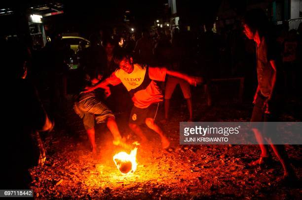 This photo taken on June 17 2017 shows youths playing fire football known locally as sepak bola api at a slum area in Surabaya Indonesia's second...