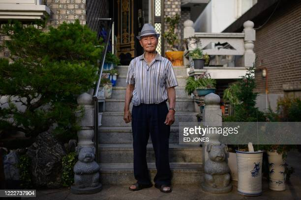 This photo taken on June 17 2020 shows North Korean refugee Kim Kunwook posing for a portrait outside his home in the 'Abai village' area of Sokcho...