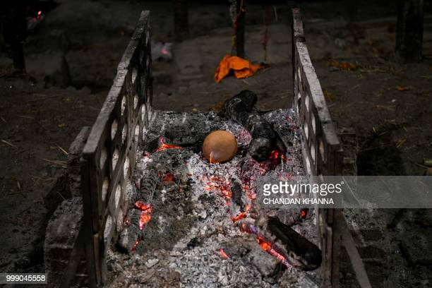 This photo taken on June 2 2018 shows a dead body burning out at the Manikarnika ghat in the old quarters of Varanasi The Doms are a small community...