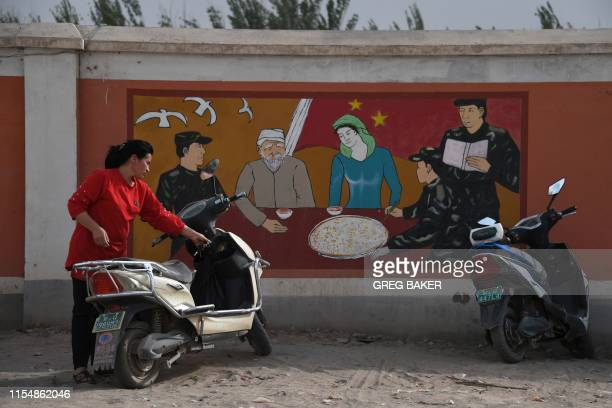 This photo taken on June 2, 2019 shows a Uighur woman beside a propaganda painting showing soldiers meeting with a Uighur family, outside a military...