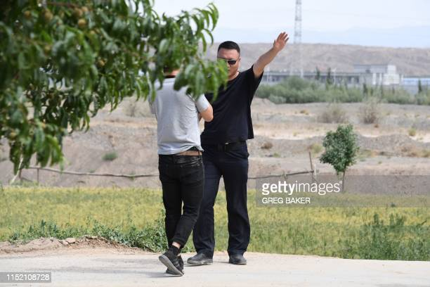 This photo taken on June 2 2019 shows an AFP video journalist being escorted away from a village while filming buildings at the Artux City Vocational...