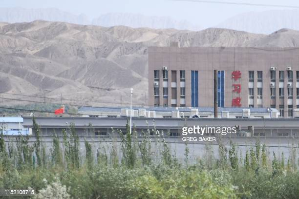 This photo taken on June 2, 2019 shows the Chinese flag and buildings at the Artux City Vocational Skills Education Training Service Center, believed...