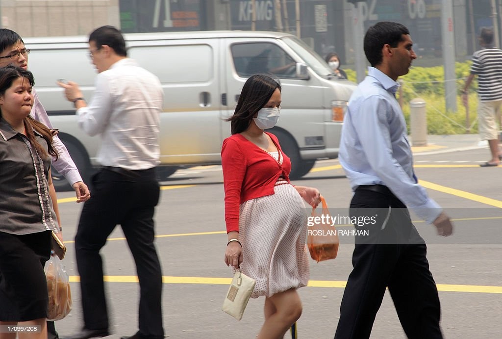 This photo taken on June 20, 2013 shows a pregnant woman with a face mask walking on the street in Singapore. Singapore's smog index hit the critical 400 level on June 21, making it potentially life-threatening to the ill and elderly people, according to a government monitoring site. AFP PHOTO/Roslan Rahman