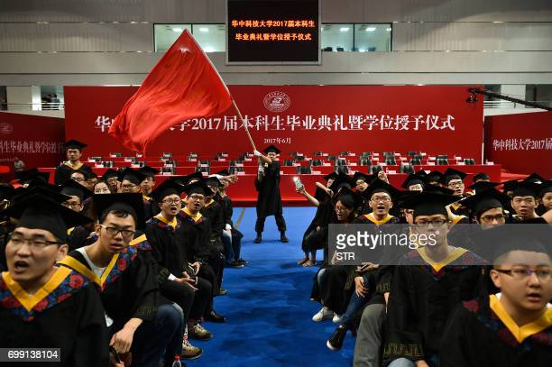 This photo taken on June 20 2017 shows a graduate waving a flag during the Huazhong University of Science and Technology graduation ceremony in a...