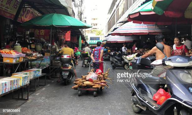 This photo taken on June 20, 2018 shows a vendor pulling a trolley with dog meat piled on top at the Dongkou market in Yulin in China's southern...