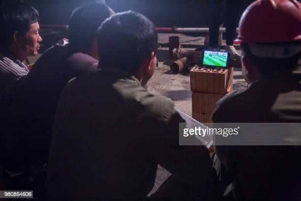 This photo taken on June 20, 2018 shows Chinese workers watching the Russia 2018 World Cup Group B football match between Portugal and Morocco on...