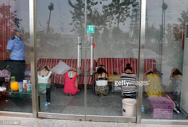 This photo taken on June 21 2011 shows a Chinese policeman watching over a group of massage girls suspected of prostitution during a raid on a...