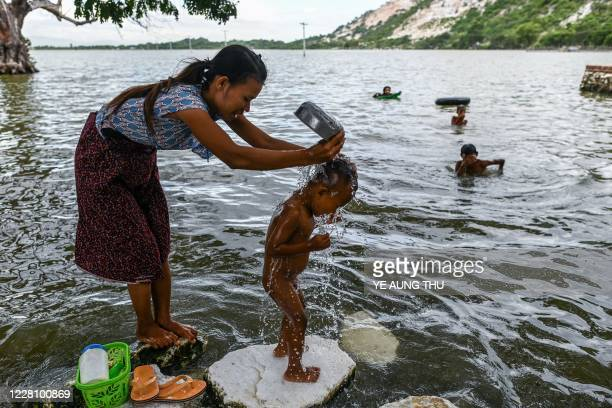 This photo taken on June 21 2020 shows a woman bathing her son next to the marble hills on the banks of the Ayeyerwady River in Sagyin village in...