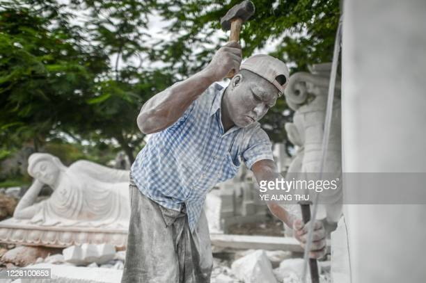 This photo taken on June 21 2020 shows a worker cutting a block of marble for a statue in Sagyin village in Madaya township about 46km from Mandalay...