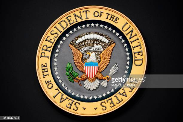 This photo taken on June 22 2018 shows the US presidential seal on the podium before the US president speaks on immigration in the South Court...