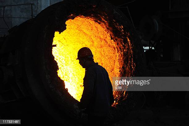 This photo taken on June 25 2011 shows a worker stoking a giant burning cauldron at a steel mill in Hefei in eastern China's Anhui province Growth in...