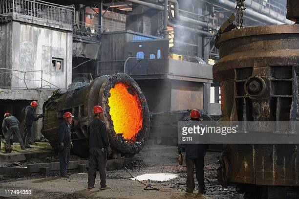 This photo taken on June 25 2011 shows employees working beside a giant cauldron at a steel mill in Hefei in eastern China's Anhui province Growth in...