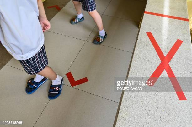 This photo taken on June 25, 2020 shows students standing next to markers for social distancing to prevent the spread of the COVID-19 novel...