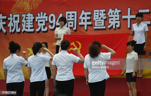 This photo taken on June 26 2015 shows people saluting the Communist Party flag at a ceremony marking the 94th anniversary of the Chinese Communist...