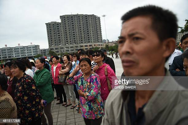 STORY 'CHINANKOREARUSSIAECONOMYDIPLOMACY' FOCUS This photo taken on June 26 2015 shows residents watching a ceremony held by the local Communist...