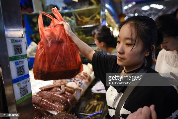This photo taken on June 27 2017 shows a woman looking at QR codes used for scanning payments at a seafood stall at a market in Beijing China was the...