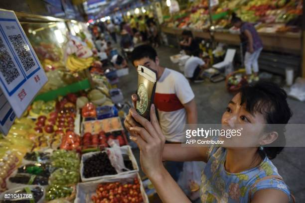 This photo taken on June 27 2017 shows a woman making purchases by scanning QR codes using her smartphone at a fruit stall in a market in Beijing...