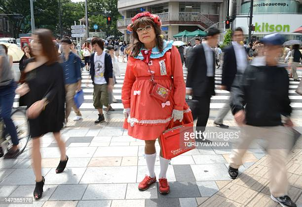 This photo taken on June 27 shows Yuzo Shiozawa a 60 year old Tokyoite dressed in a handmade costume of cartoon heroine Candy posing on a street at...