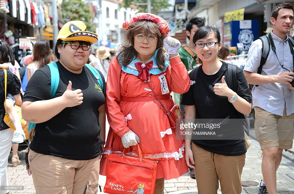 This photo taken on June 27, shows Yuzo Shiozawa (C) a 60 year old Tokyoite dressed in a hand-made costume of cartoon heroine Candy posing with tourists on a street at Harajuku fashion district in Tokyo. Candice 'Candy' White Ardlay is the main character of a hugely popular cartoon anime series originally launched in Japan in the 1970s and set in the United States during the early 20th century. AFP PHOTO / Toru YAMANAKA
