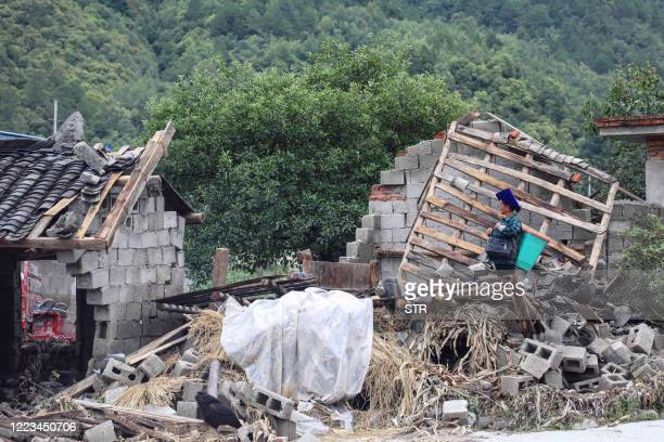 This photo taken on June 28, 2020 shows a woman looking at the aftermath of flooding caused by heavy rainfall in Mianning county, in the Liangshan Yi...